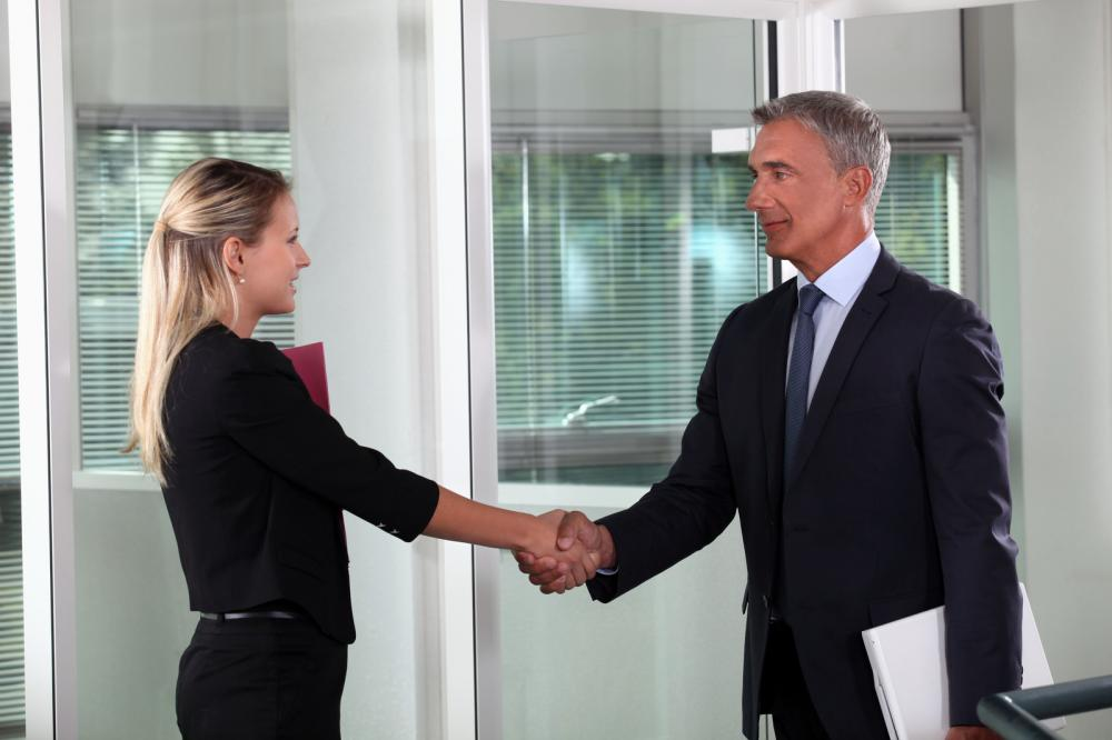 Self-assured mature manager shaking the hand of a successful female candidate after assessing her learning quotient